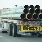 Oversize Load sign on back of truck carrying steel or fiberglass pipes Mexicom Logistics